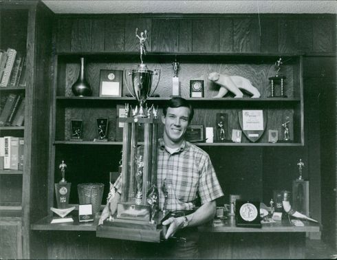 Bob Seagren holding his huge trophy, behind him are his other trophies.  - May 1966