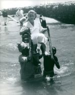 Woman sitting on a chair, smiling, carried by two men, to the sea in Yemen. October 1962.