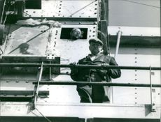Reginald Calvert looking down from a deck, another man looking out from a window.