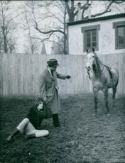 Man helping Irène Tunc to stand up after falling down from the horse.