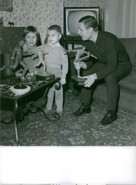 Man with his children, playing with toys.