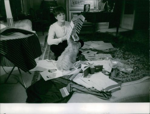 Simone Micheline Bodin sitting on carpet with her dog while reading.  - Oct 1960