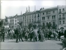 People gathered on road, looking something. 1959