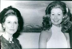 Margrethe II looking towards the camera and smiling with another woman.1971