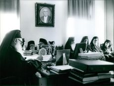 Athenagoras I writing at his desk, other Greek-othodox priests sits on the background.