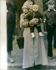Susan Hampshire  holding a child.