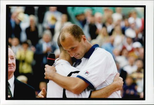 American tennis player Andre Agassi hugs Andrei Medvedev after finishing him in the French Open 1999