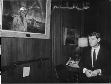 """Robert Francis """"Bobby"""" Kennedy standing in front of his own portrait hanging on wall."""
