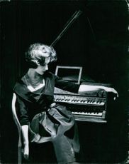 A photo of a woman standing beside piano. Photo taken in 1959.