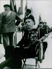 Close up of a soldier sitting on chair in street during an event.