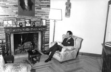 Carlos Hugo, Duke of Parma sitting and reading beside the fireplace, 1964.