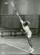 Tennis player Stan Smith is serving the ball.