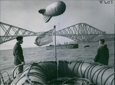 two soldiers are watching a huge balloons that balloons hovering over the Forth Bridge during World War II. 1942.