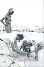 Albert II of Belgium making castle with his children on sand.