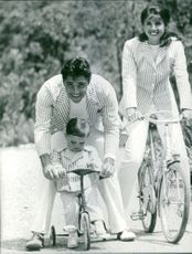 Sacha Distel riding cycle with his family.