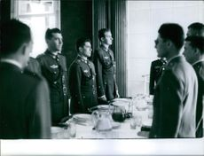 Juan Carlos with his fellow military men standing before the dining table, 1959.