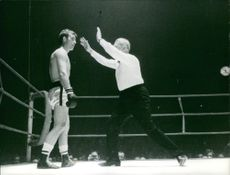 Referee showing gesture and talking to boxer.