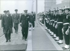 People moving forward during an event, soldiers standing beside and saluting them.