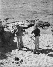 French actress Jeanne Moreau and Fashion designer Pierre Cardin walking along the sands.