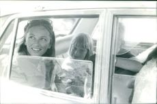 Queen Paola of Belgium with her children and looking out through the car's window.
