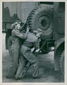 Two women labor to push a giant tire in the back of a truck.