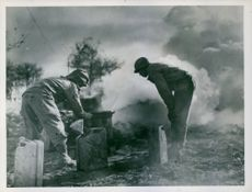 Sheltered by a heavy smoke screen, U.S. Army engineers concentrate on a bridge building project across the Moselle River in France.