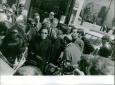 Press reporters talking to a man and photographers taking pictures.