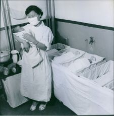 A nurse carrying a newly born baby inside a nursery room.