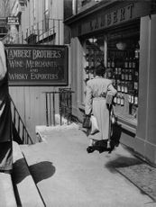 A woman looking at the window shop of a wine store.