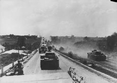 Military tanks thronging the both sides of road.
