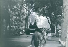 Soldiers gathered in the street, passing by tank.