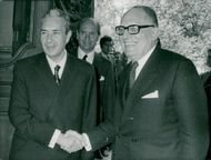 Italy's Foreign Minister Aldo Moro shakes hands with Maurice Schumann