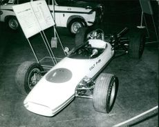 A photo of a race car displayed in a car show.