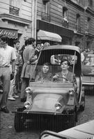 A young man with a young woman on a passenger seat driving a small car on a busy street.