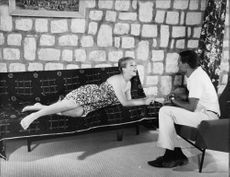Marina Vlady lying on couch, talking to man.