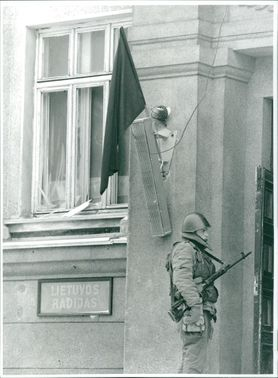 Soviet soldier is guarding outside Vilna radio station