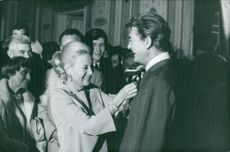Michelle Morgan with some people smiling and helping Jean Marais with his tie.