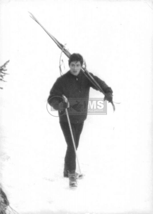 Brigitte Bardot`s husband Jacques Charrier walking on snow with his skis.