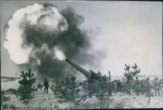 Soldiers firing through the cannon during wartime.