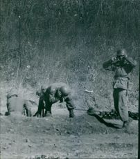 Soldiers standing together and covering their ears, due to sound of blast.