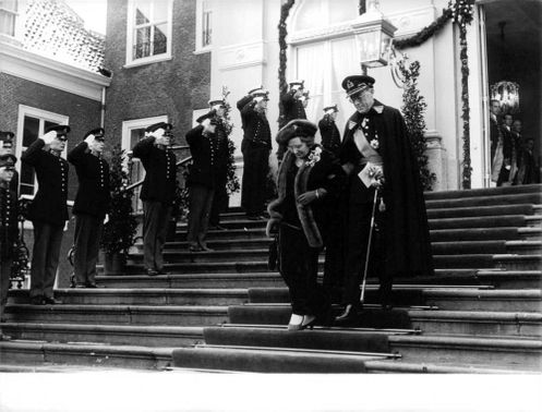 Queen Juliana and husband Prince Bernhard descending the stairs.