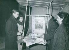 A couple talking to a woman on a newspaper stall.