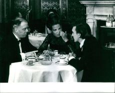 Two men and a woman having a conversation in front of a dining table, 1968.