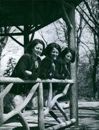Three women standing together and smiling.