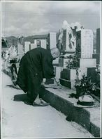 Man standing and touching a tomb in the cemetery.