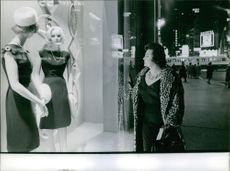 A photo of an Italian lirico-spinto soprano popular in the post-war period Renata Tebaldi looking at display mannequin wearing a black dress in a store. 1963