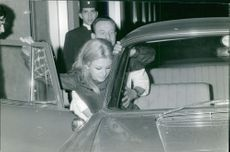 A woman named Sandra Ellilo being assisted by a man in getting inside a car.  Taken - 17 May 1967