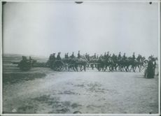 Group of soldiers riding in horse carts in street.