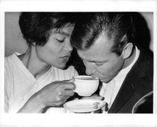 Eartha Mae Kitt having tea with man.