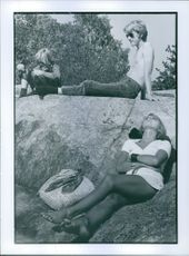 Boy and girls siting relaxing on the rock during picnic.  They go out to relax.